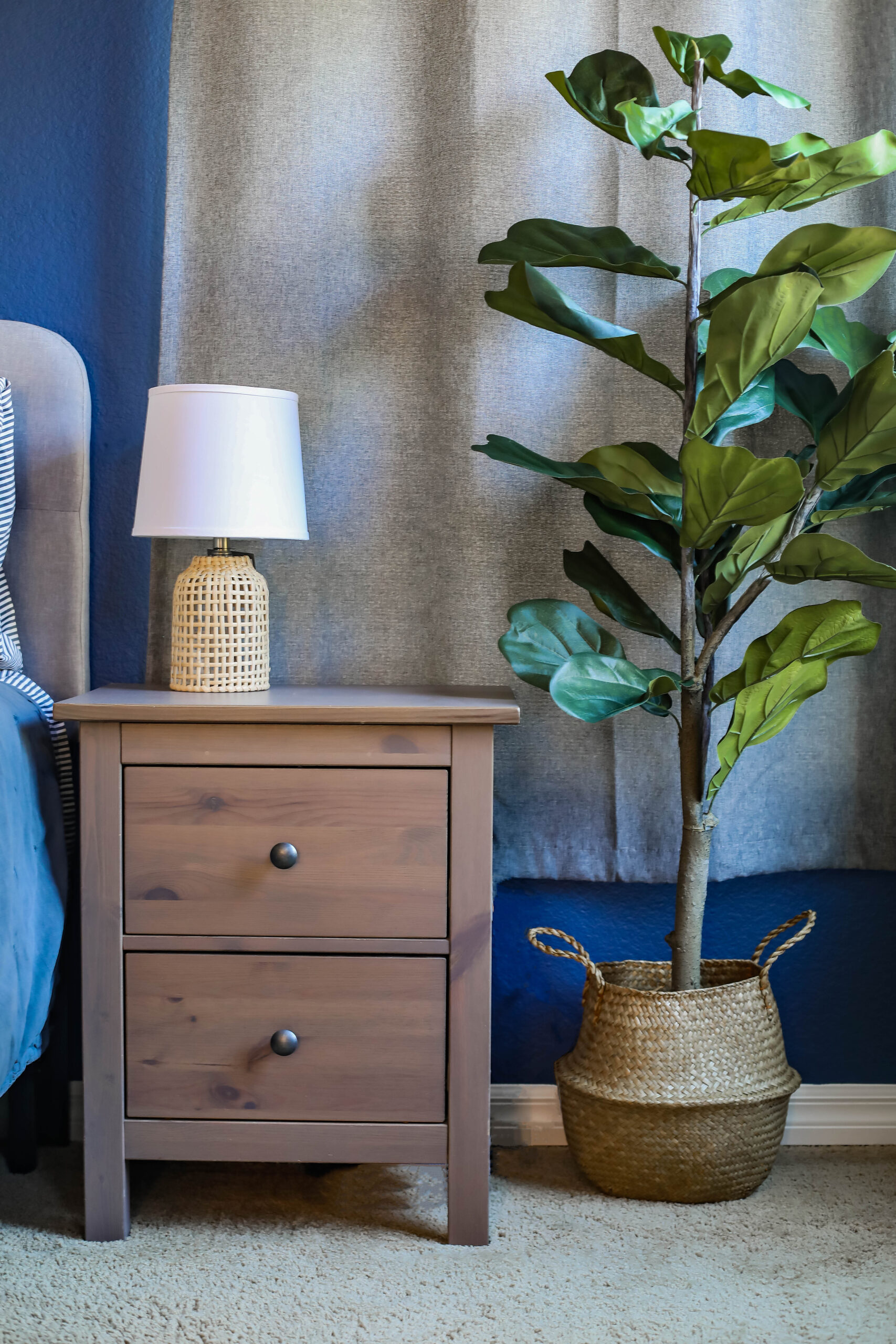 Looking for navy and grey bedroom decor? I love how the faux fiddle leaf tree adds a pop of color to the bedroom, and those rattan lamps are PERFECT!
